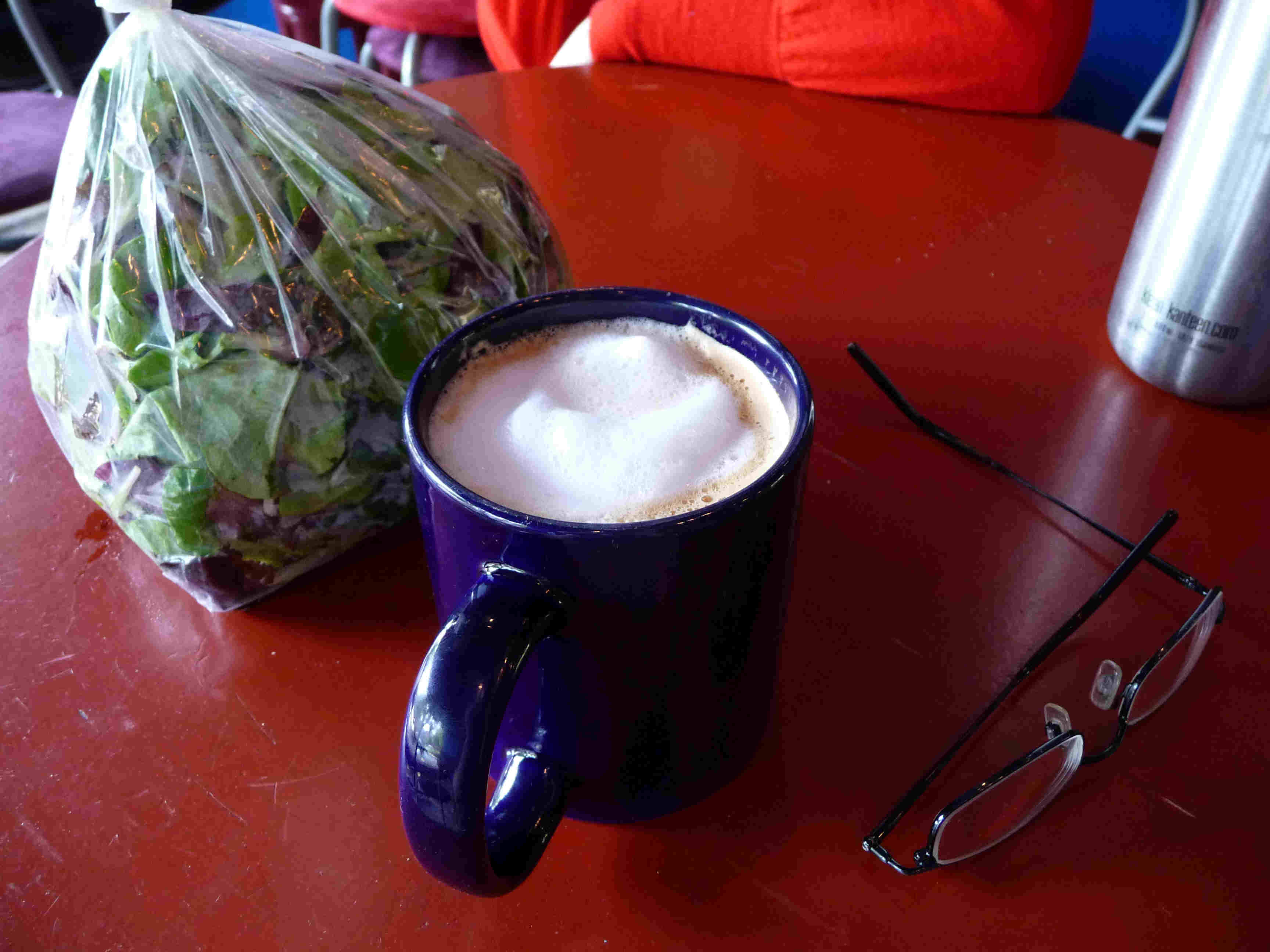 A cappuccino next to some mixed greens.